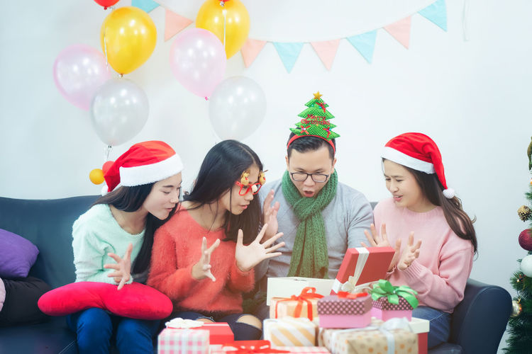 Cheerful Family Opening Gift Box While Sitting On Sofa At Home