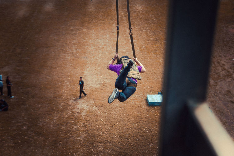High Angle View Of Woman On Swing At Playground Seen Through Window