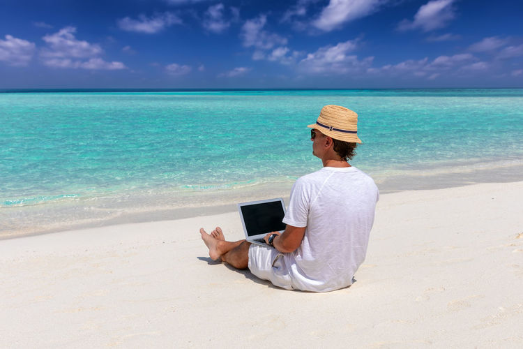 Rear view of man using laptop at beach against sky