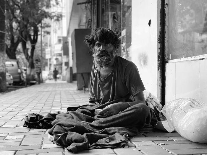Portrait of beggar sitting on street