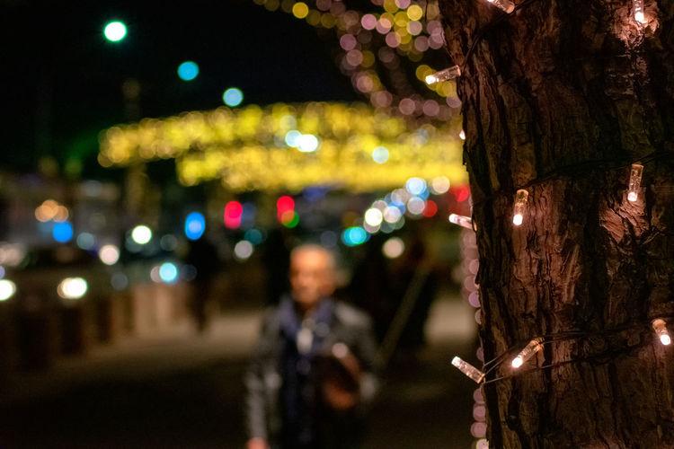 Portrait of man on illuminated tree at night