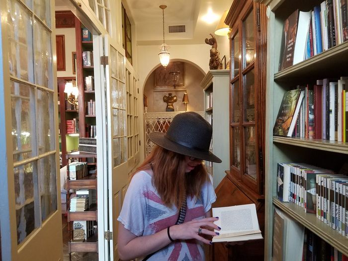Bookworm in her Habitat Reading Bookstore Hats Redhead Indoors  One Person Young Adult People Sitting Adult Young Women Only Women EyeEmNewHere EyeEm Ready
