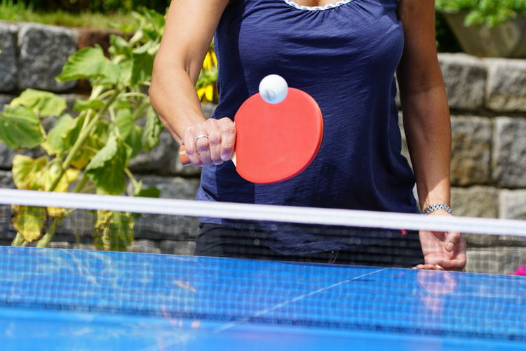 Holding One Person Midsection Table Tennis Lifestyles Casual Clothing Leisure Activity Day Playing Sport Ball Adult Real People Women Focus On Foreground Standing Relaxation Nature Outdoors