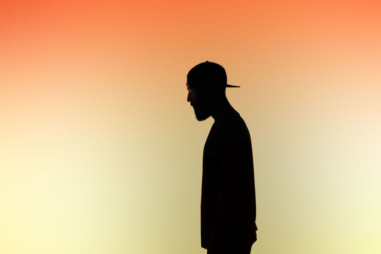 Side view of silhouette man against colored background