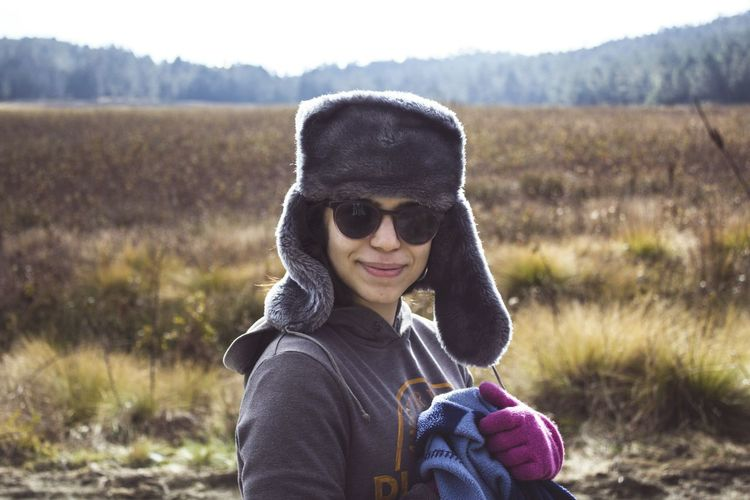 Portrait Of Smiling Young Woman Holding Wearing Warm Clothing On Field