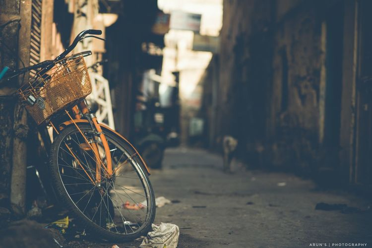 Old bicycle on alley amidst buildings in city