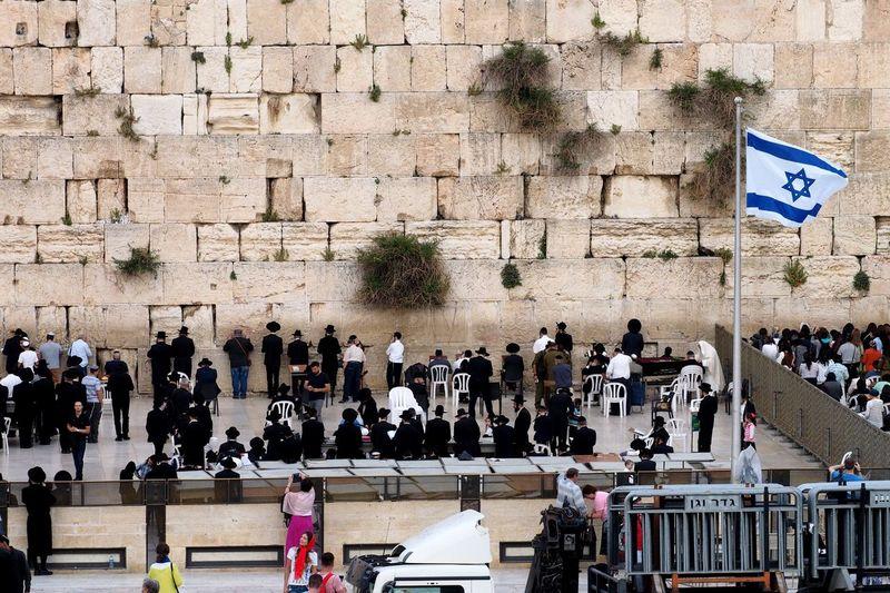 Israel flag waving amidst crowd by wailing wall