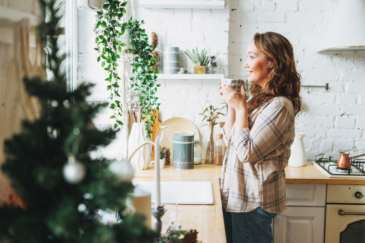 Attractive smiling woman with curly hair in plaid shirt with the cup of tea near window