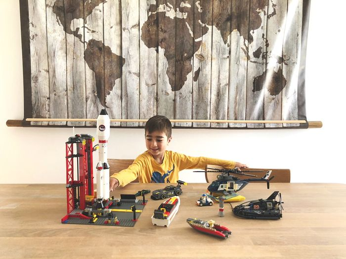 Boy playing with toys on table against world map at home