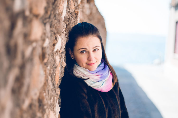 Portrait of beautiful woman smiling while standing by wall