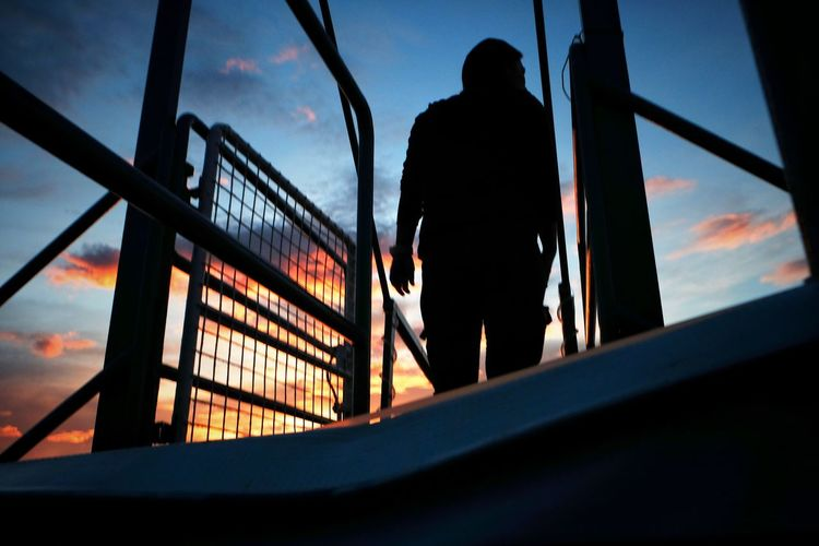 Rear view of silhouette man on railing against sky