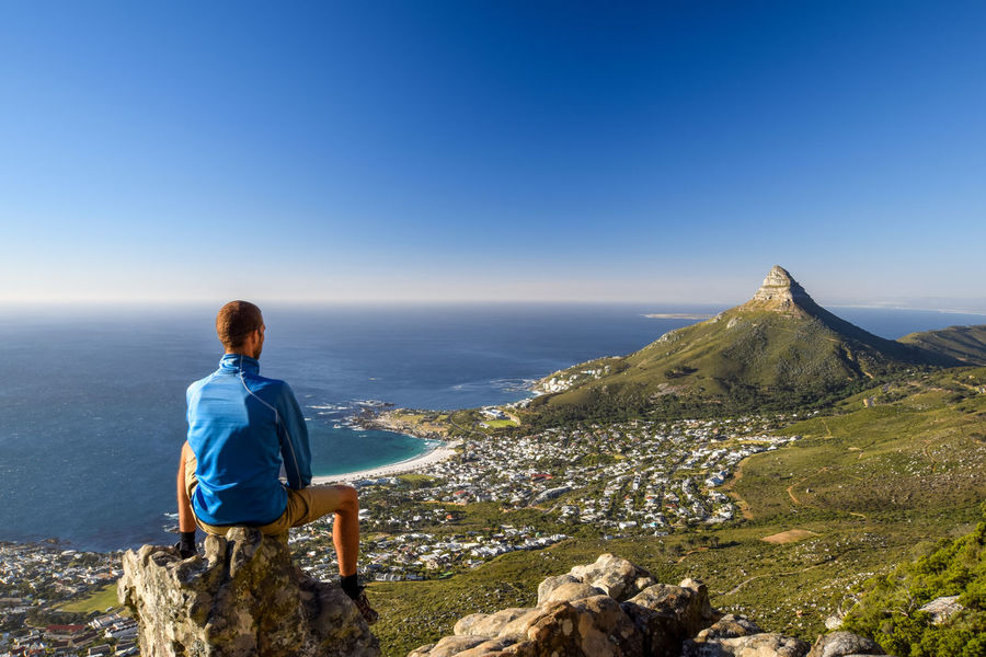 Young male hiker sitting on a rock at Kasteelspoort Hiking Trail in Table Mountain National Park, Cape Town, South Africa, pointing at the suburb of Camps Bay and Lion`s Head mountain in background. Camps Bay Cape Town Happy Hiking Holiday Lions Head Panorama Rear View Serenity South Africa Travel Western Cape Adventure Africa Beach Hiker Hiking Trail Kasteelspoort Leisure Activity Mountain Ocean One Person Sport Travel Destinations Young Man First Eyeem Photo EyeEmNewHere