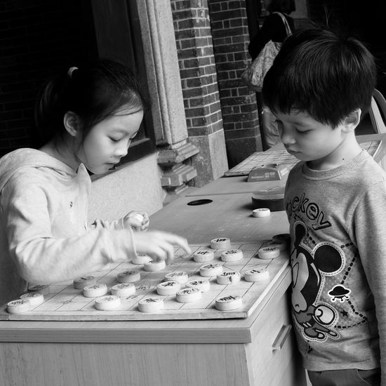 Young Chinese Chess Players , Friendship is teaching each other New Games. Two People Childhood Child Leisure Activity Bonding Togetherness Real People Waist Up