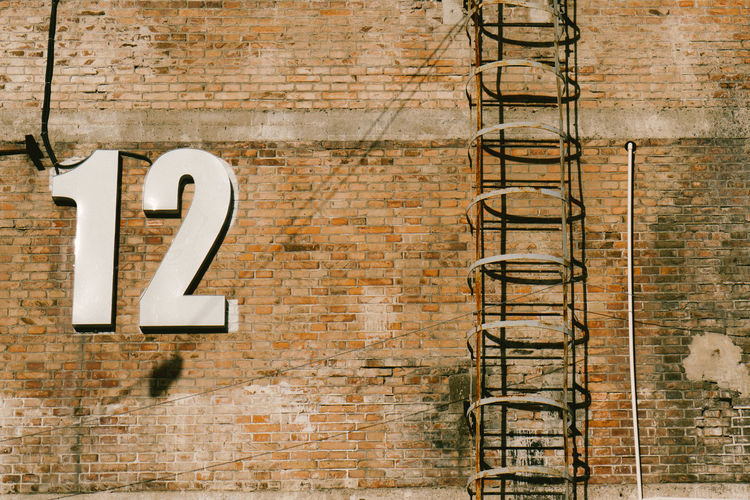 Low angle view of numbers by ladder on brick wall