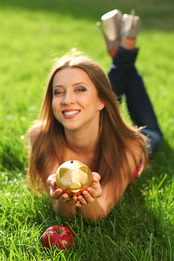 Woman in the park on the green grass with moneybox Hairstyle Outdoors Day Emotion Leisure Activity Lifestyles Young Adult Portrait Women Green Color Happiness Land Nature One Person Real People Smiling Front View Field Plant Grass Holding Young Women