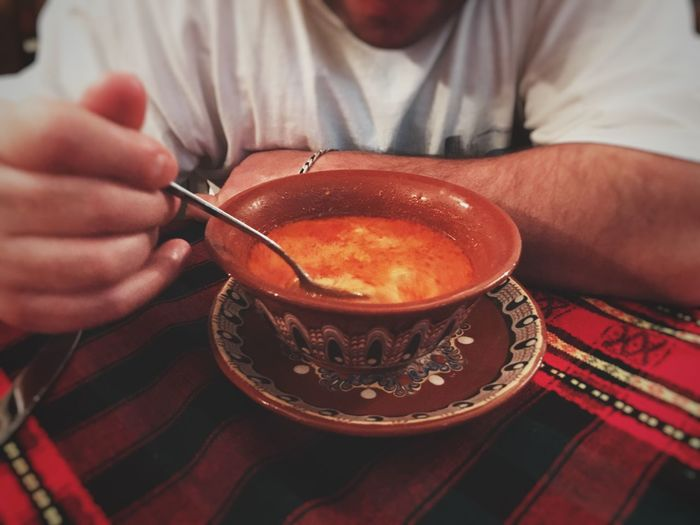 Midsection Of Man Eating Fresh Tripe Soup In Bowl On Table