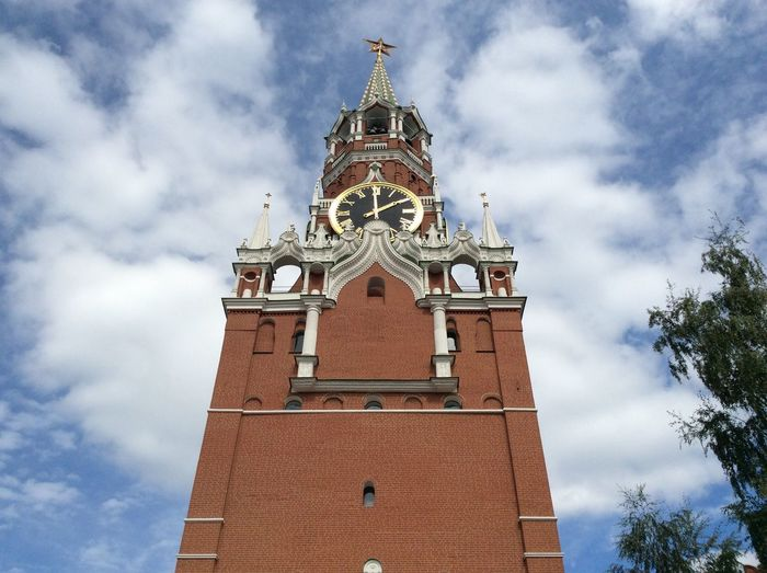 Low angle view of spasskaya tower against cloudy sky