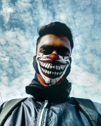 Portrait of person wearing mask against sky during winter