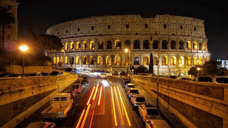 Illuminated street against historic colosseum