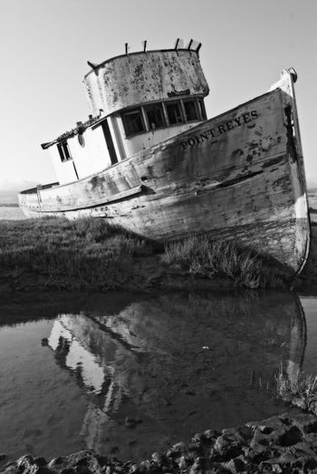 Damaged boat in sea against sky