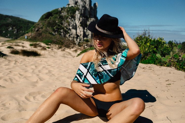 Hat Land One Person Beach Young Women Young Adult Leisure Activity Clothing Real People Lifestyles Sand Three Quarter Length Sitting Nature Beauty Beautiful Woman Day Sunlight Relaxation Wireless Technology Hair Outdoors Hairstyle Fashion Sun Hat