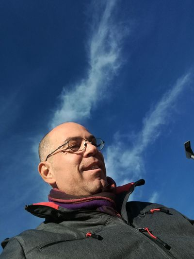 Low Angle View Of Man Standing Against Blue Sky During Sunny Day