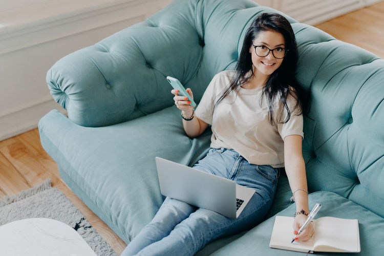 Portrait of young woman with mobile phone and laptop working on sofa