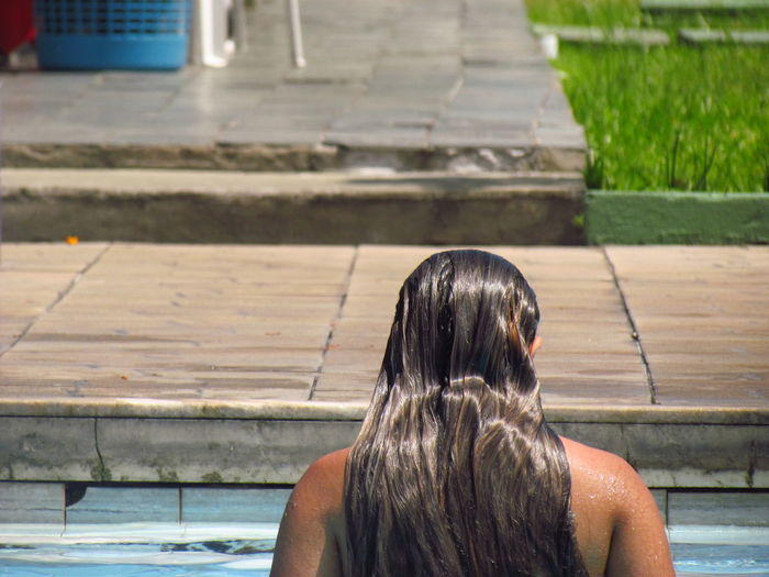 Rear View Of Young Woman Relaxing At Poolside