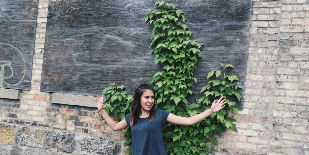 Portrait of young woman standing by brick wall
