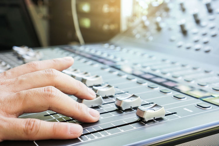 Cropped hand mixing music in recording studio