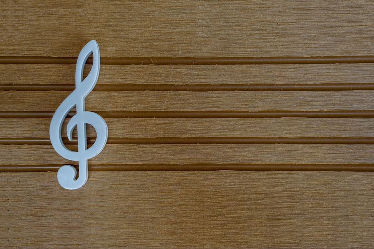 White Plastic G-clef on wooden music Staff Audio Classic Music Staff Art Classical Clef Hobby Instrument Melody Musical Note Sheet Wooden