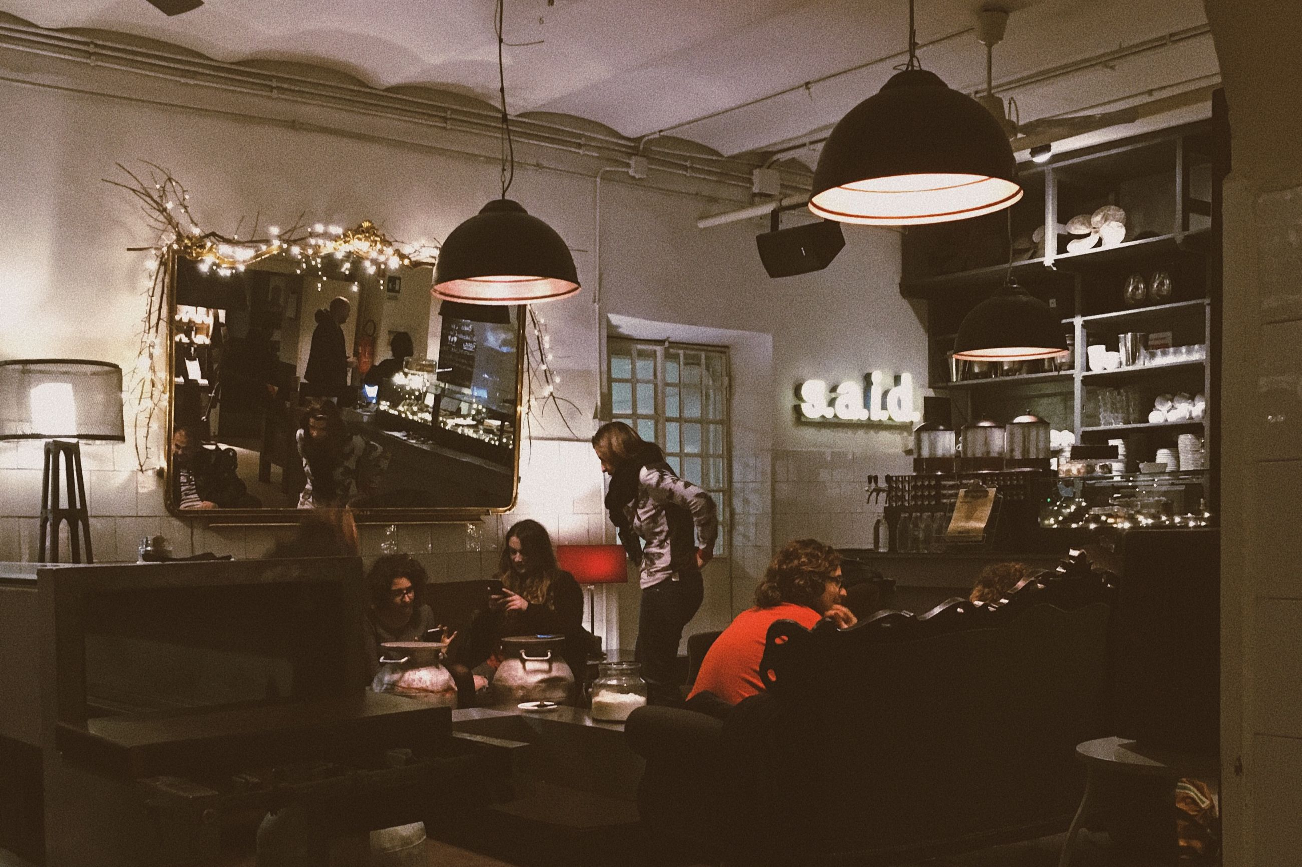 GROUP OF PEOPLE AT ILLUMINATED STORE