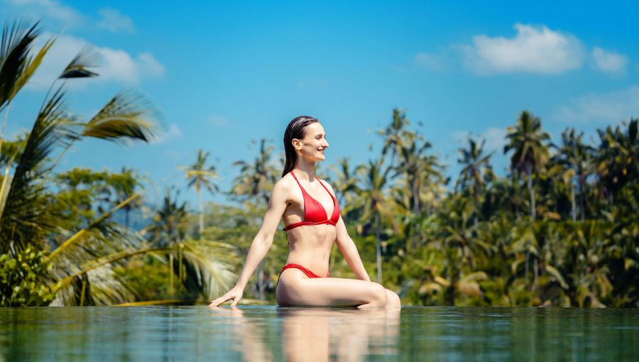Beautiful woman sitting at infinity pool against trees and sky