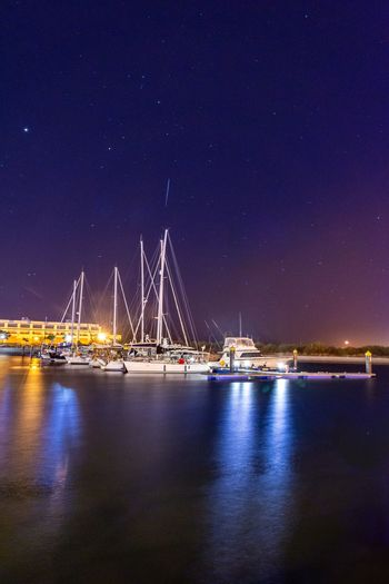 Sailboats in sea against sky at night