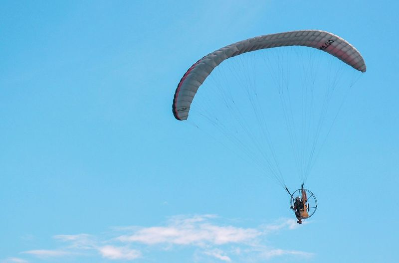 Parachute Extreme Sports Adventure Paragliding Sky Sport Mid-air Flying Gliding Nature Blue Day Leisure Activity Transportation Low Angle View Exhilaration Real People Freedom One Person