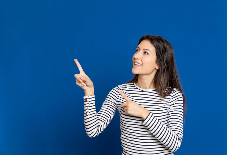 Young woman gesturing while standing against blue background