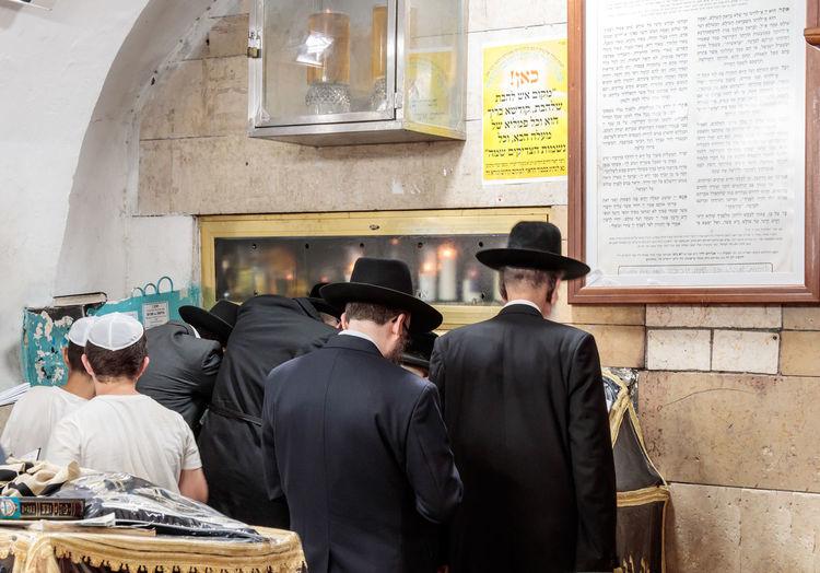 Rear view of jews praying in synagogue