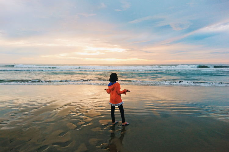 Rear view of girl standing against sea during sunset