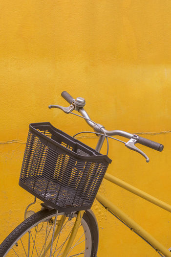 Close-up of bicycle parked against yellow wall