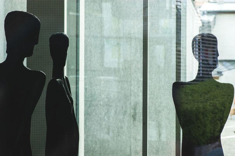Bronze statues by glass window