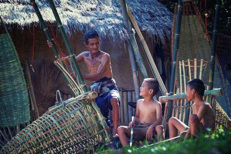 Shirtless Grandfather With Grandchildren Making Wicker Basket Outside Hut