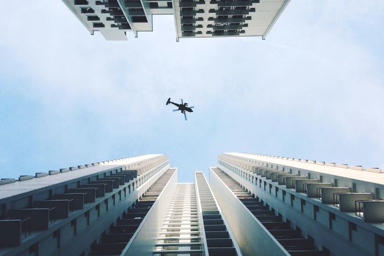 Directly below shot of helicopter flying over buildings against sky