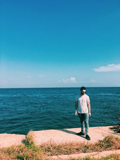 Full Length Of Man Standing Against Sea And Sky During Sunny Day
