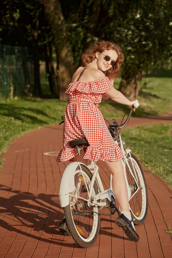 Rear view portrait of woman riding bicycle