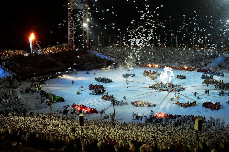 High angle view of people on illuminated shore against sky at night