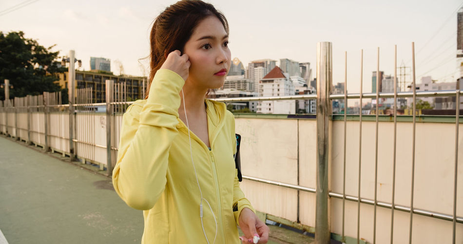 Young woman listening music while standing on road