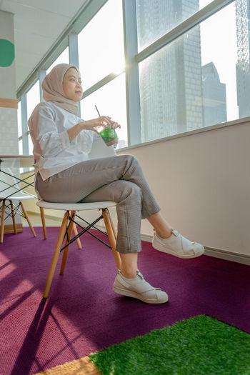 Woman sitting on chair in corridor