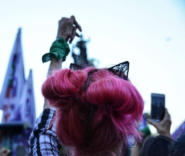 Rear view of woman with pink hair against sky