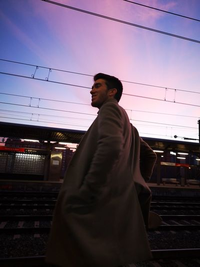 Man standing at railroad station platform against sky during sunset