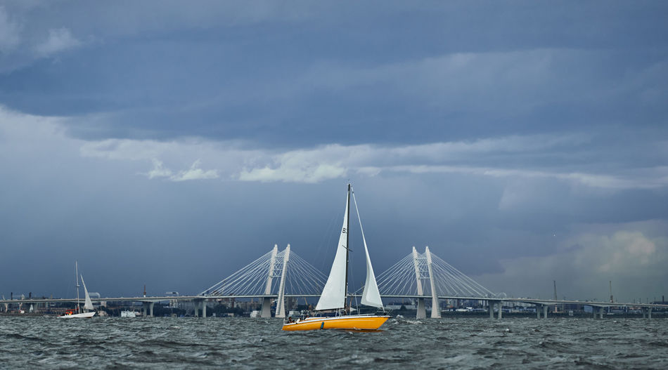 Sailboats on bridge over sea against sky